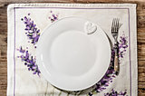 Plate and fork laid on vintage wooden dining table