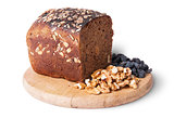 Bread with seeds on wooden board with raisins and nuts