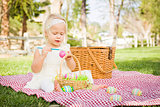 Cute Baby Girl Coloring Easter Eggs on Picnic Blanket