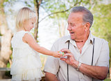 Cute Baby Girl Handing Easter Egg to Grandfather Outside