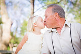 Grandfather and Granddaughter Kissing At The Park