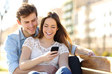 Couple sharing media in a smart phone in a park