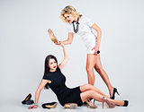 Studio fashion shot: confrontation of two lovely women (blonde a