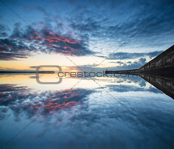 Beautiful vibrant sunrise sky over calm water ocean with lighthouse