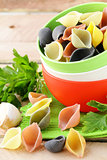 uncooked tricolor pasta in bowl on a wooden table