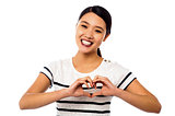 Pretty woman making heart symbol with hands