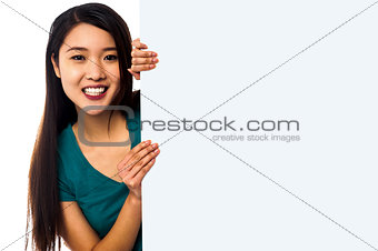 Asian girl holding blank white ad board