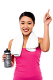 Smiling fitness woman holding sipper bottle