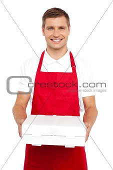 A chef in red uniform offering you a pizza box