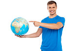 Handsome young caucasian pointing at globe