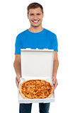 Smiling man offering pizza to you