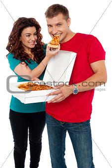 Caring girlfriend making her boyfriend eat pizza
