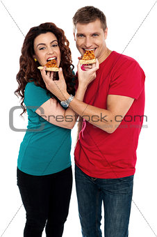 Adorable love couple enjoying pizza pie together