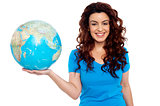 Pretty smiling girl holding globe in right hand