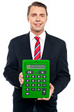 Young businessman showing big green calculator