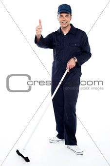 Cleaning guy holding broom and showing thumbs up