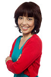Side pose of smiling asian woman, arms crossed