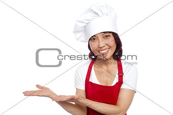 Smiling asian chef gesturing guests to take their seats