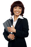 Smiling female executive holding binder