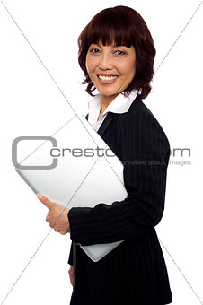 Asian corporate female holding laptop