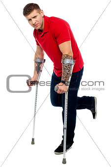 Painful expression of young guy walking with help of crutches