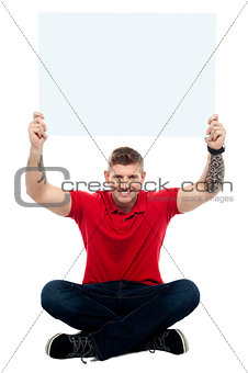 Casual man sitting on floor with billboard raised above head
