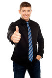 Smart young executive showing thumbs up