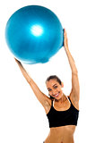 woman holding big blue pilates ball above her head