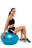 Pretty woman relaxing on big blue exercise ball