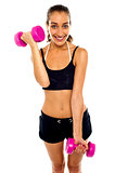 Smiling fit woman working out with dumbbells