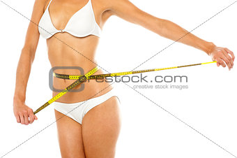 Fit woman measuring her waist, cropped image
