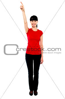 Beautiful female model directing finger upwards