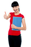 Pretty teenager holding notebook and gesturing thumbs up