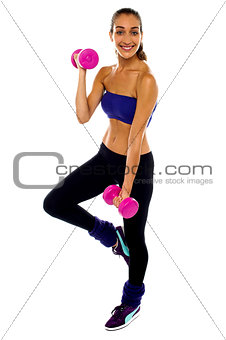 Slim young woman working out with dumbbells