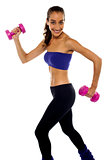 Slim beauty in walking posture, holding dumbbells