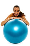 Woman leaning over big blue swiss ball