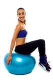 Pretty lady sitting on big blue exercise ball