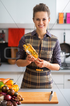 Portrait of happy young housewife with corn