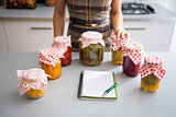 Closeup on notepad and young housewife with jars of pickled vege