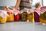 Closeup on jars of pickled vegetables and housewife writing in n