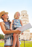 Happy mother and baby girl sightseeing in front of leaning tower