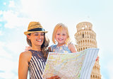 Mother and baby girl looking in map in front of leaning tower of