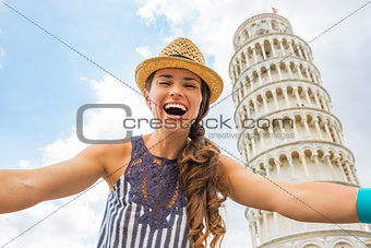 Portrait of young woman making selfie in front of leaning tower