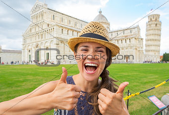 Portrait of happy young woman showing thumbs up on piazza dei mi
