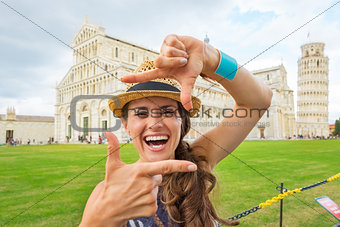 Portrait of happy young woman framing on piazza dei miracoli, pi