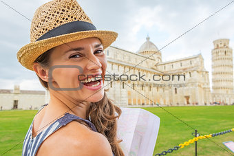 Portrait of smiling young woman with map on piazza dei miracoli,