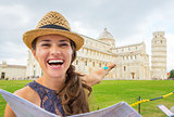 Happy young woman with map pointing on duomo di pisa, pisa, tusc