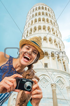 Portrait of happy young woman with photo camera in front of lean