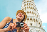 Happy young woman with photo camera in front of leaning tower of