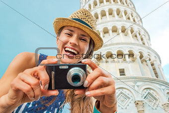 Portrait of smiling young woman with photo camera in front of le